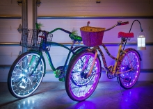 Two bikes with glowing neon lights on their wheels sit side by side.