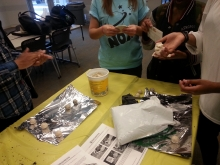 Ms Dolores demonstrates to teens in Afterschool Lounge how to make a seed bomb