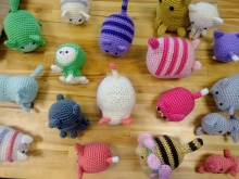 Picture of scattered crocheted cats on a wooden table