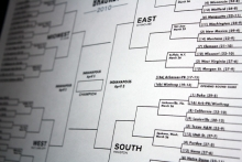 A piece of paper shows March Madness brackets
