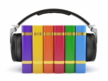 Picture of pair of headphones, with rainbow colored books between the earpads