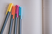 yellow, orange, pink, and blue pens set on an open blank notebook