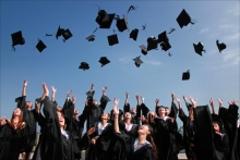 Image of graduating students throwing their caps into the sky