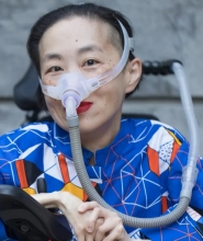 Photo of an Asian American woman in a power chair. She is wearing a blue shirt with a geometric pattern with orange, black, white, and yellow lines and cubes. She is wearing a mask over her nose attached to a gray tube and bright red lip color. She is smi