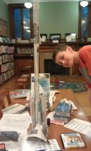 Daniel posing with his newspaper tower