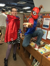 Children's librarian Ms. Jenny with a red cape and Asad dressed as the Scarlet Spider, perched on a bookshelf