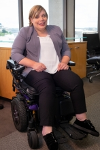 A white woman with short blonde hair wears a business suit, sits in a black and purple power chair