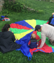 several small children sit on a multicolored parachute spread on the grass in a park
