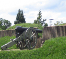 An old cannon surrounded by greenery at Fort Stevens