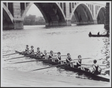 Women's eight and coxswain on the water at the boathouse, circa 1920s