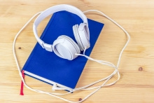 Picture of blue book with a pair of white headphones plugged into the the book to symbolize an audiobook.