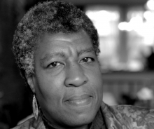 Black and white photo of author Octavia Butler. The author is slightly smiling.