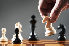 A hand manipulating the white knight above a chess board