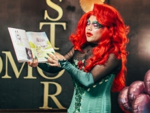 Photo of drag queen Santa Domingx reading