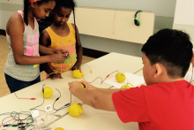 Children working with lemons and conductive wires as part of a Maker activity at DCPL