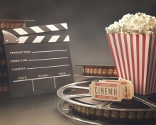 Clapperboard, popcorn, cinema tickets and a movie reel, computer illustration