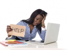 "A woman at a laptop holing up a sign that says ""help"""