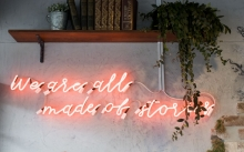 "A pink neon sign that says ""we are all made up of stories"""