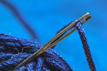 The magnified end of a needle is threaded with a brilliant blue yarn, which can also be seen.