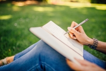 woman's hand writing on notepad in park