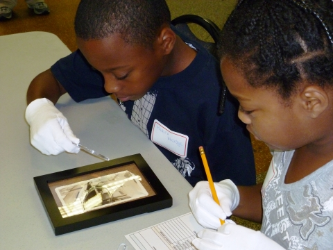 Boy and girl examine artifact