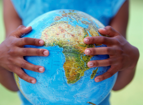 Image of child's hands holding a globe