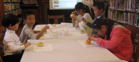 Kids painting mini pumpkins