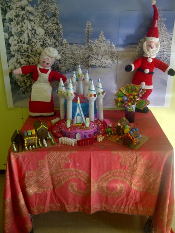 A Candy Castle cake with Mr. and Mrs. Santa Claus against a snowy forest background