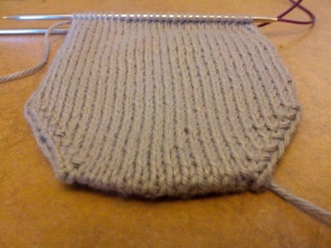 half-knitted grey sock on knitting needles