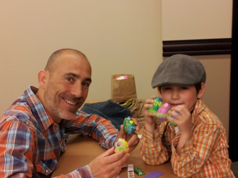 father and son with decorated plastic eggs