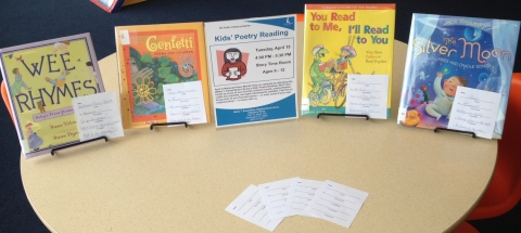 Poetry display featuring children's poetry books, haiku poems, and a flyer for the Kids' Poetry Reading