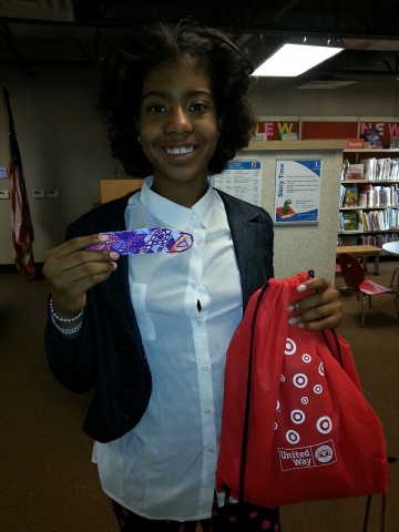 Picture of Treasure B., her bag of books, and her winning bookmark