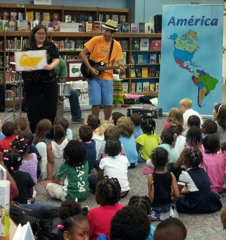 Andres and a children's librarian performing in front of children