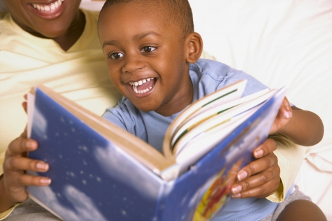 Child and adult reading a book together