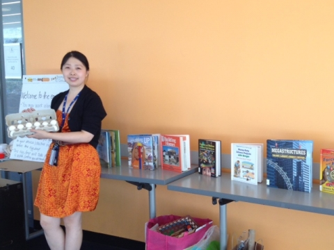 Theresa Wang, Children's Librarian, holding a carton of eggs next to a selection of science-related books
