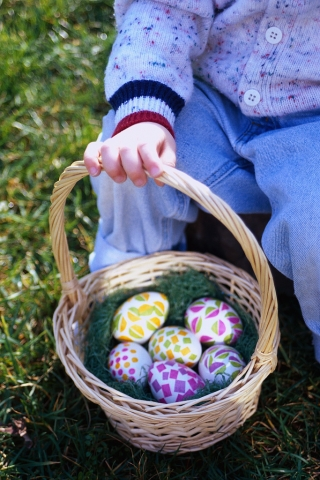 child holding basket of eggs.