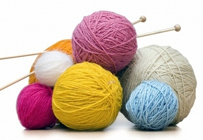 photograph of knitting needles and colorful yarns