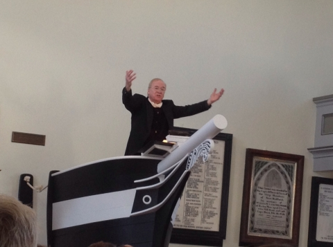 """A preacher reads in the Seamen's Bethel, site of a chapter in """"Moby-Dick."""""""