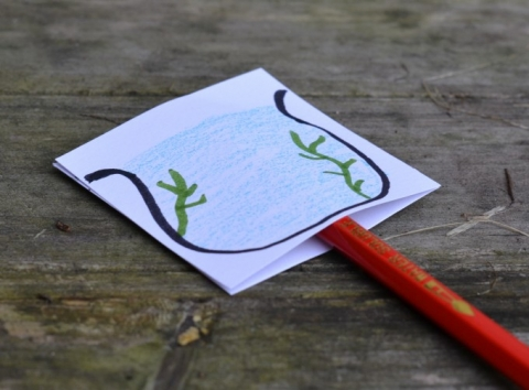 Picture of a pencil with a piece of cardstock with a drawing of a fishbowl on top of it