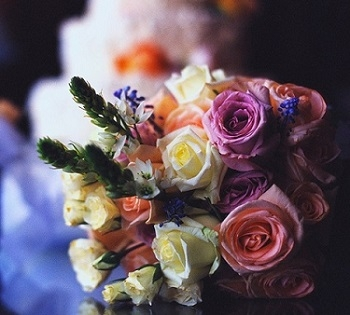 Photograph of a bouquet with a cake in the background