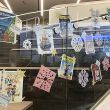 Books cover artwork displayed on glass of library stairwell