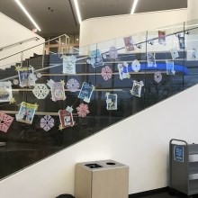 Book cover artwork displayed along the glass of a library stairwell