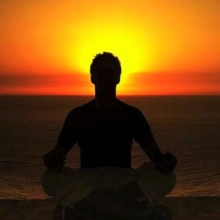 Image of person meditating at sunset