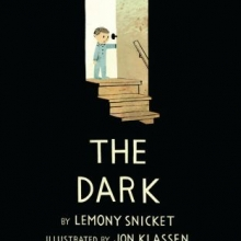 The Dark cover: a boy in pajamas opening a backlit door to a dark basement where nothing is illuminated.