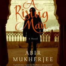 A rising man cover in which a man in silhouette stands in front of a stone railing carved in an Indian style