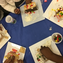 photo of kids' hands making gingerbread houses