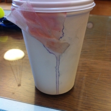 photo of a paper cup with and tea bag dripping tea down the side