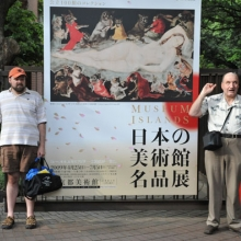 Two men, one in shorts and the other in pants, standing outside on either side of a large sign with a colorful painting on it, Asian characters and English words saying