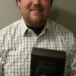 Photograph of Adult Summer Reading 2013 grand-prize winner Sean Ballantine holding his new Kindle Tablet.