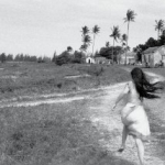 The back of a little girl running in field towards houses